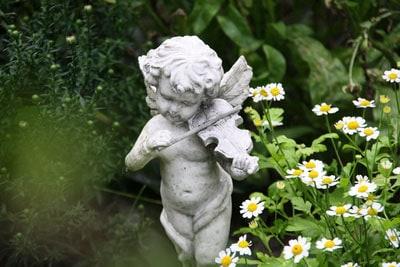 Eine Geige spielende Putte im Garten