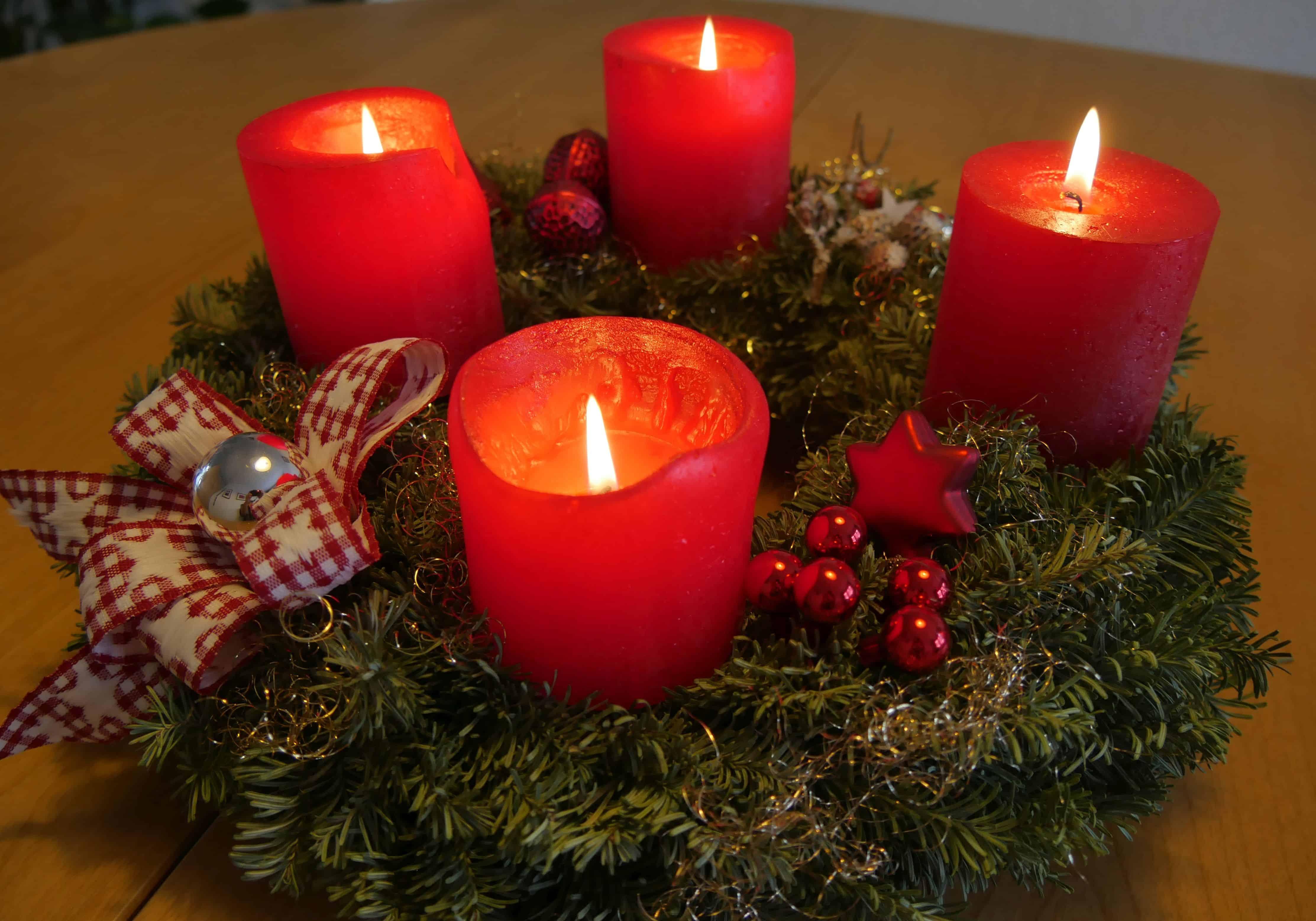 Ein Adventskranz mit vier brennenden Kerzen
